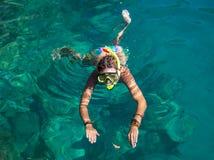 Kvinna med maskeringen som snorklar i klart vatten Arkivbild