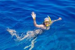 Kvinna med maskeringen som snorklar i klart vatten Fotografering för Bildbyråer