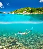 Kvinna med maskeringen som snorklar i klart vatten Arkivfoton