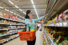 Kvinna med matkorgen och smartphone på lagret Royaltyfri Foto