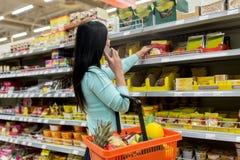 Kvinna med matkorgen och smartphone på lagret Royaltyfri Fotografi