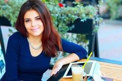 Kvinna med minnestavladatoren som dricker kaffe Royaltyfri Foto