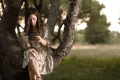 Kvinna med minnestavlan på ett träd fotografering för bildbyråer