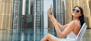Kvinna med minnestavlaPC som solbadar över stadspöl arkivfoto