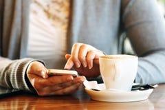 Kvinna med mobilen i kafé Arkivbild
