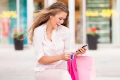 Kvinna med mobiltelefon- och shoppingpåsar Arkivfoton