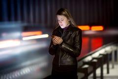 Kvinna med mobiltelefonen som går på natten bredvid huvudvägen royaltyfri foto