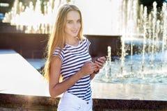 Kvinna med mobiltelefonen utomhus fotografering för bildbyråer
