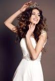 Kvinna med mörkt hår i elegant klänning med den lyxiga kronan Royaltyfria Bilder