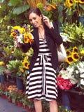 Kvinna med near blommor för mobiltelefon Royaltyfri Foto