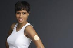 Kvinna med nikotinlappen på armen arkivbild
