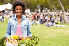 Kvinna med ny jordbruksprodukter som köps på den utomhus- bondemarknaden Royaltyfri Foto