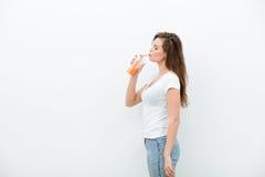 Kvinna med orange fruktsaft royaltyfria bilder