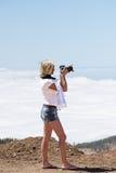 Kvinna med ovannämnda moln för kamera som shhoting naturen Arkivfoton