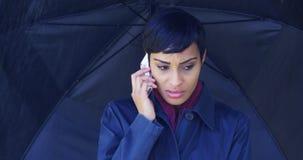 Kvinna med paraplyanseende i regn genom att använda mobiltelefonen royaltyfri fotografi