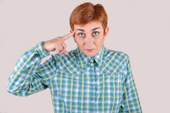 Kvinna med pekfingret på hennes huvud Arkivfoto