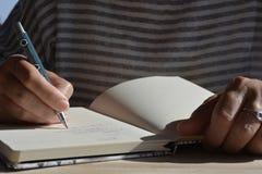 Kvinna med pennan i handen som skriver i en tidskrift arkivbild