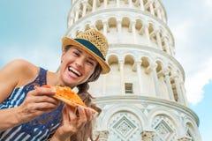 Kvinna med pizza som är främst av lutande torn av pisa Royaltyfria Bilder