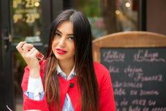Kvinna med röda kanter som visar läppstift, utomhus coffee shopbakgrund arkivbild