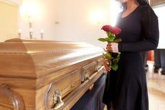Kvinna med röda rosor och kistan på begravningen Fotografering för Bildbyråer