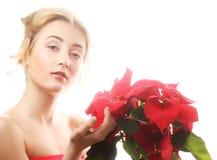 Kvinna med röda xmas-blommor arkivbild