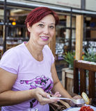 Kvinna med rött hår som har frukosten arkivbilder