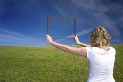 Kvinna med ramen på stor äng fotografering för bildbyråer
