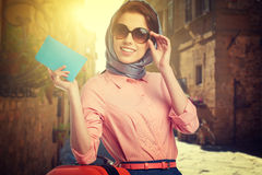 Kvinna med resväskan på gatan arkivfoto