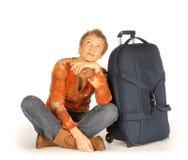 Kvinna med resväskan som ser upp Arkivfoto