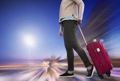 Kvinna med resväskan som väntar på flygplan royaltyfri bild