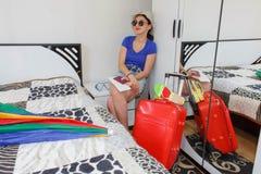 Kvinna med resväskasammanträde på nightstand i hotell Arkivfoton