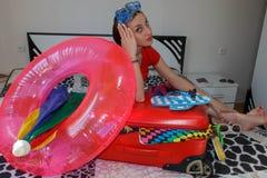Kvinna med resväskasammanträde på säng i hotell Få klart för att resa till t royaltyfri foto