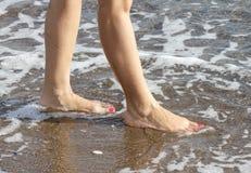 Kvinna med rosa nailpolish som går på stranden royaltyfria bilder