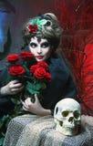 Kvinna med rosor och skallen Arkivbild
