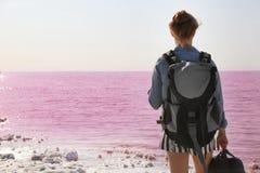 Kvinna med ryggsäcken på kust royaltyfria foton