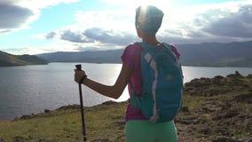 Kvinna med ryggsäcken som fotvandrar med solsignalljus lager videofilmer