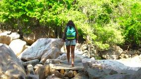 Kvinna med ryggsäcken som går på bron över floden, medan klättra i berg Resande kvinna som går på upphängning stock video