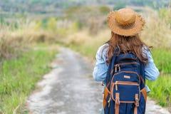 Kvinna med ryggsäcken som går på vandringsledet i natur arkivfoto