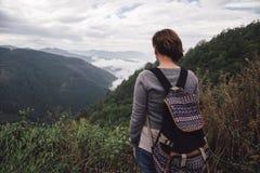 Kvinna med ryggsäcken som står fjällnära Arkivfoton