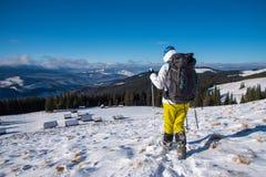 Kvinna med ryggsäcken som trekking i vinterberg royaltyfri foto