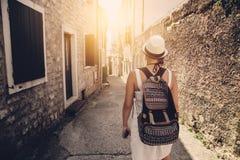 Kvinna med ryggsäcklopp som går på den gamla stadgatan Arkivfoto