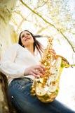 Kvinna med saxofonen i natur Royaltyfri Fotografi