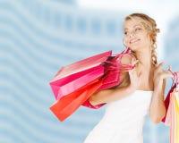 Kvinna med shoppingpåsar i klänning fotografering för bildbyråer