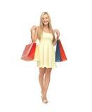 Kvinna med shoppingpåsar i klänning och höga häl Royaltyfri Fotografi