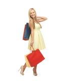 Kvinna med shoppingpåsar i klänning och höga häl Royaltyfri Foto
