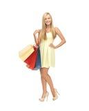 Kvinna med shoppingpåsar i klänning och höga häl Arkivfoto