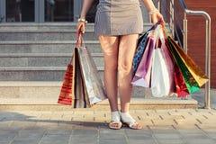Kvinna med shoppingpåsar mot en galleria Fotografering för Bildbyråer