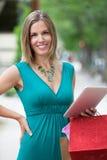 Kvinna med shoppingpåsar och den Digital tableten royaltyfri bild