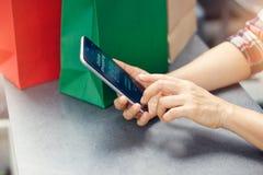 Kvinna med shoppingpåsar på tabellen, genom att använda den smarta telefonen royaltyfri fotografi