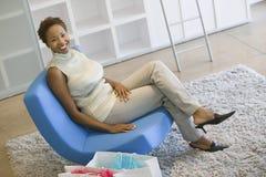 Kvinna med shoppingpåsar som kopplar av på stol Royaltyfri Bild